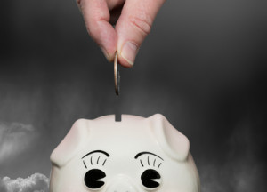 Saving money in piggy bank with fingers